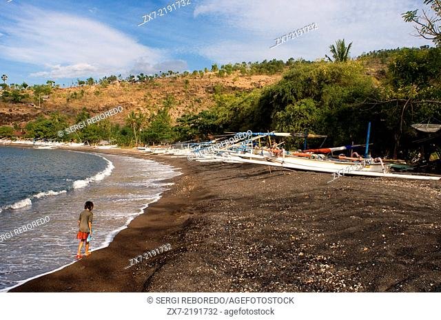 The boats rest on the sandy beach of Amed, a fisherman village in East Bali. Amed is a long coastal strip of fishing villages in East Bali