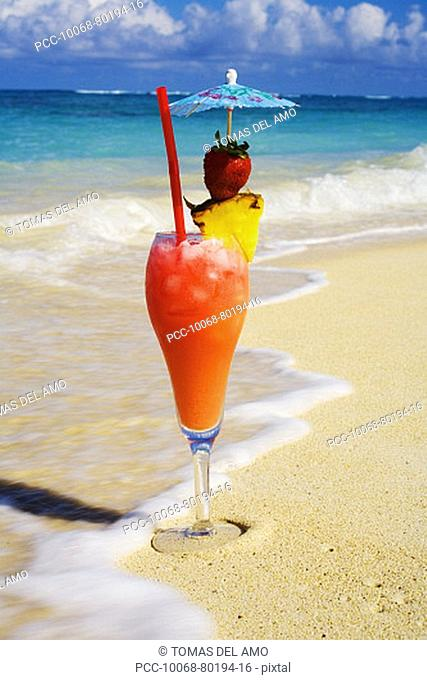 A tropical cocktail on the beach, wave washing on the sand