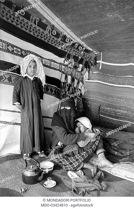 A woman and two children are in a Bedouin tent. Kuwait, December 1956