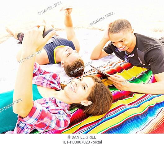 Young people lying on blanket, using technology