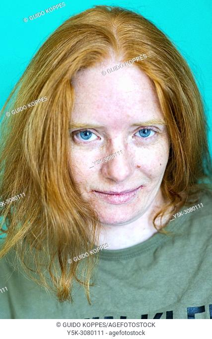 Tilburg, Netherlands. Studio-portrait of a redhaired woman wearing a branded shirt against a green background