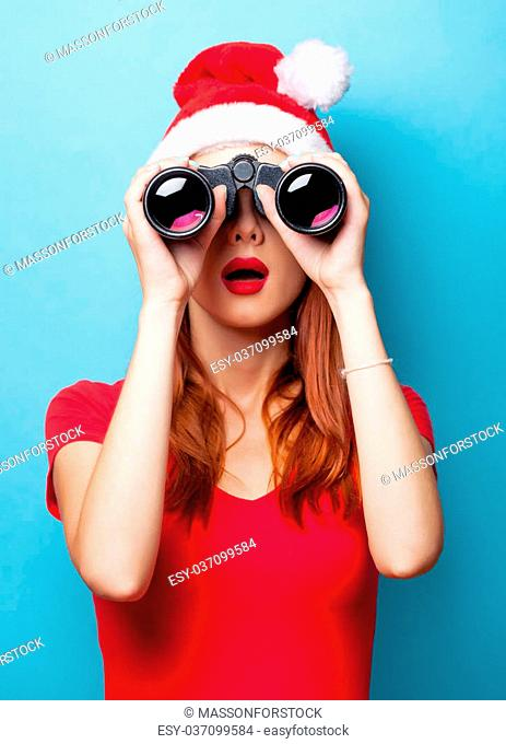 women in christmas hat with binocular on blue background
