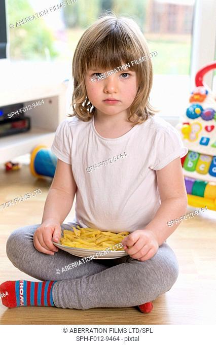 MODEL RELEASED. Young girl sitting on the floor with a plate of french fries