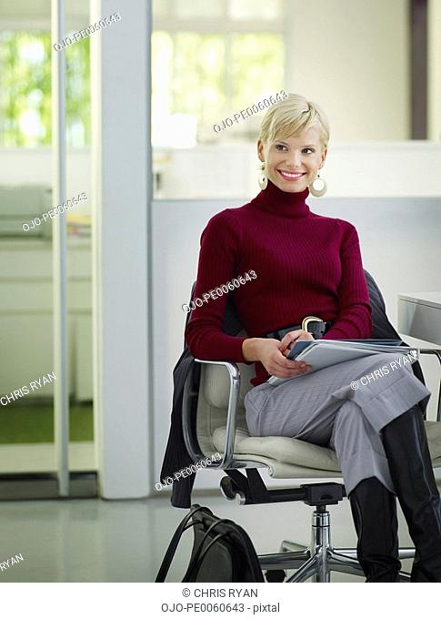 Businesswoman sitting in office with paperwork