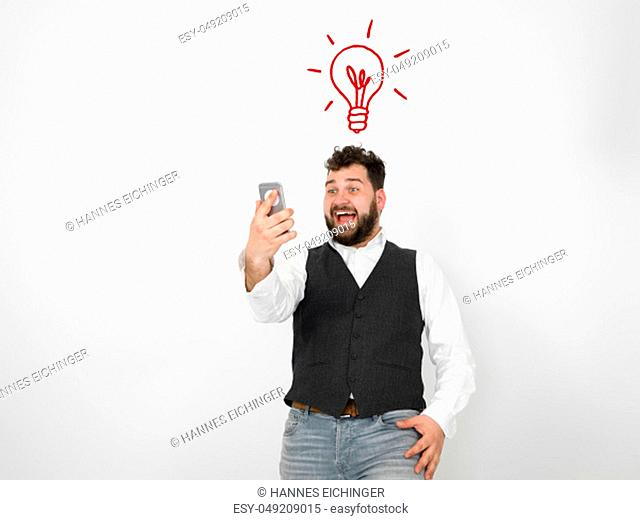 young man with black beard is posing and looking at his smartphone in front of white background