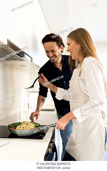 Happy couple preparing spaghetti in their kitchen