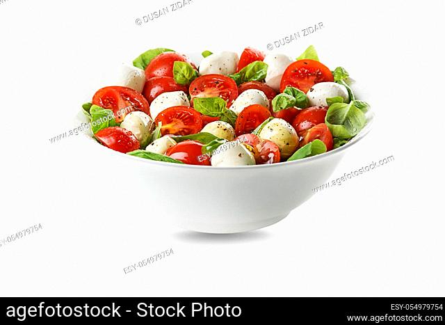 Delicious caprese salad with ripe tomatoes and mozzarella cheese with fresh basil leaves. Italian food. Salad with mozzarella, tomatoes, basil, salt