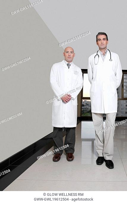 Portrait of two male doctors standing in a hospital corridor