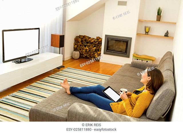 Beautiful young woman working with a tablet at home