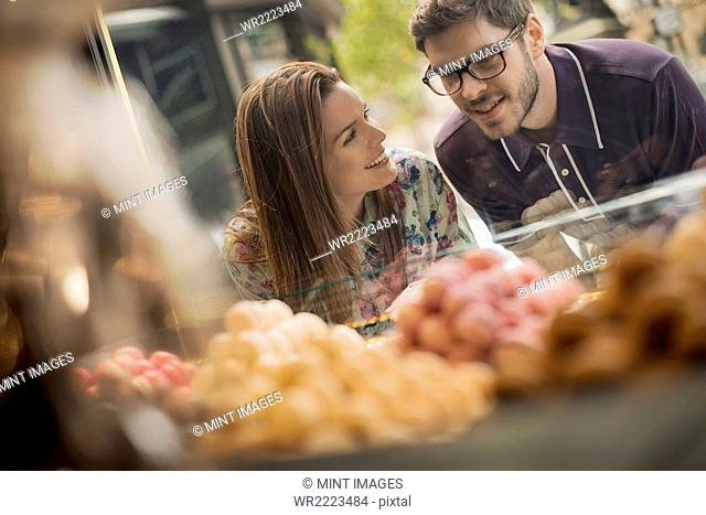 A couple looking at the window display in a confectionery shop