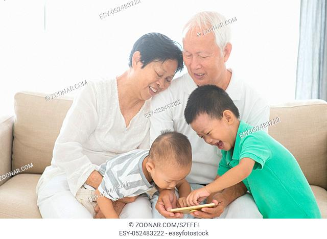 Portrait of happy Asian grandparents and grandchildren using smart phone at home, family indoor lifestyle