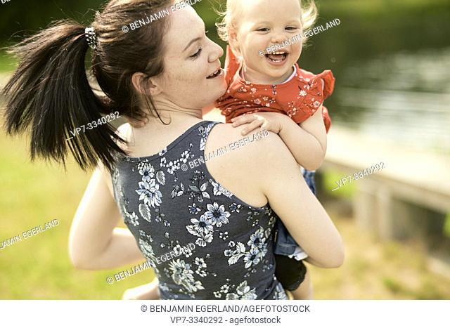 lively mother with baby toddler daughter outdoors in park