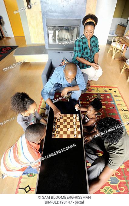Black family watching chess game