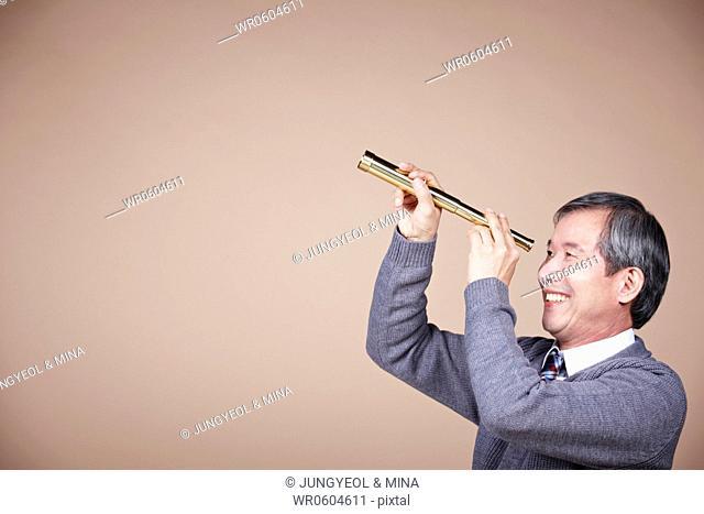 An old man looking through telescope