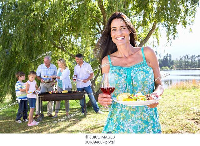 Multi-Generation Family Enjoying Barbeque By Lake