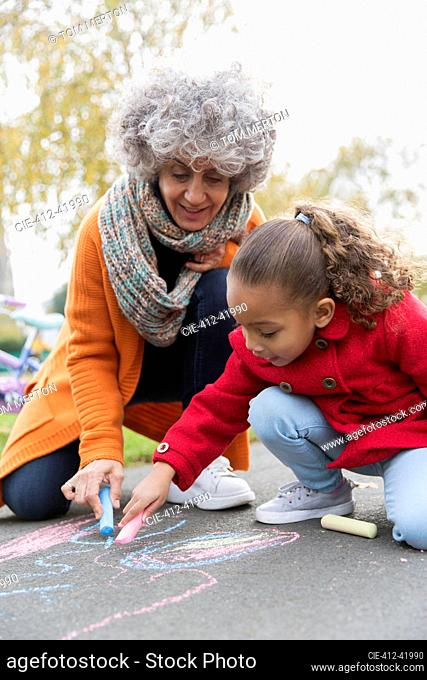 Grandmother and granddaughter drawing with sidewalk chalk