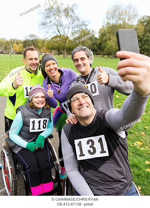 Man in wheelchair taking selfie with friends at charity race in park