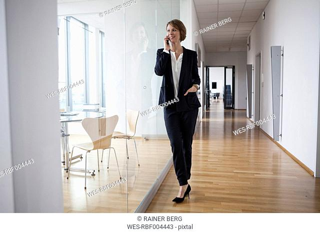 Businesswoman on cell phone in office hall