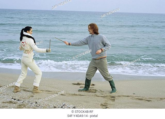 Young Couple fighting with little Sticks - Imitation of a Swordplay - Fun - Leisure Time - Beach