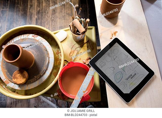 Cup and tools on pottery wheel near digital tablet