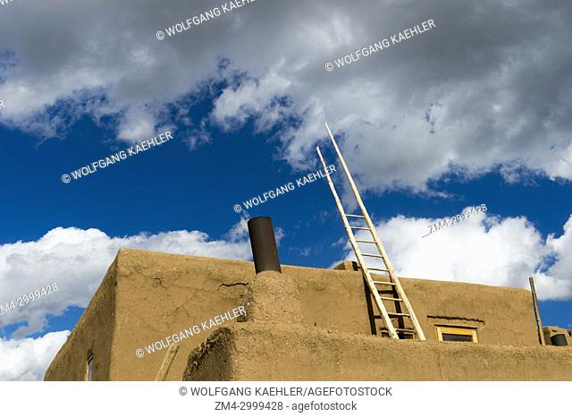 Ladders being used to move to different levels of the Taos Pueblo which is the only living Native American community designated both a World Heritage Site by...