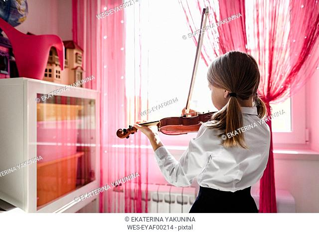 Girl playing violin at the window at home