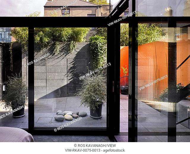 Interior view of living area showing glass doors to courtyard. K House, Ranelagh, Ireland. Architect: Architects Tom Maher, 2016