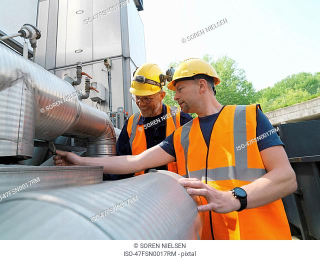 Workers examining machinery on site
