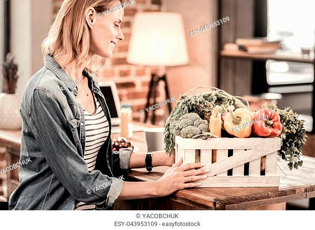 Healthy food. Joyful nice delighted woman looking at the vegetables and smiling while taking the box