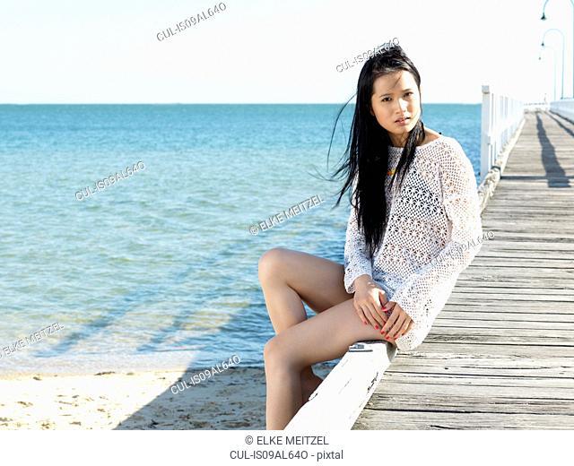 Portrait of young woman sitting on pier, Port Melbourne, Melbourne, Victoria, Australia