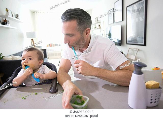 Father watching baby son eating