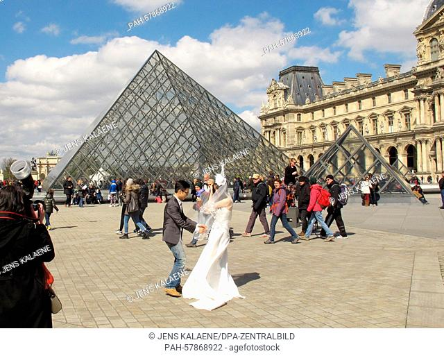 Tourists and visitors walk past the glass pyramid, the main entrance area to the Louvre museum in Paris, France, 5 April 2015