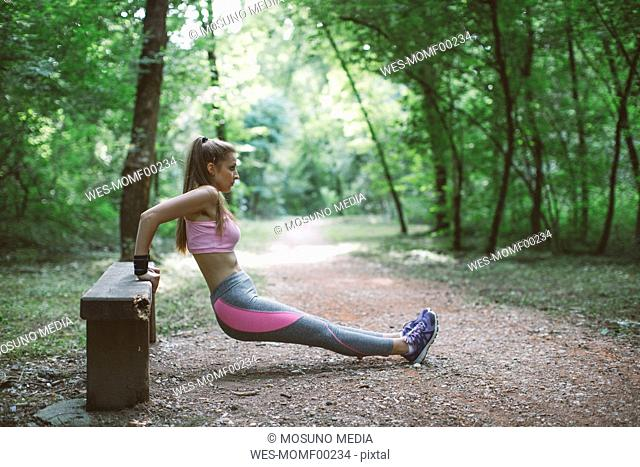 Young woman exercising on a bench in forest