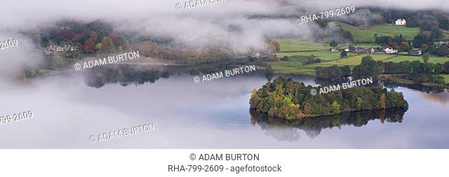 Grasmere lake and village appears through swirling morning mist, Lake District Narional Park, Cumbria, England, United Kingdom, Europe