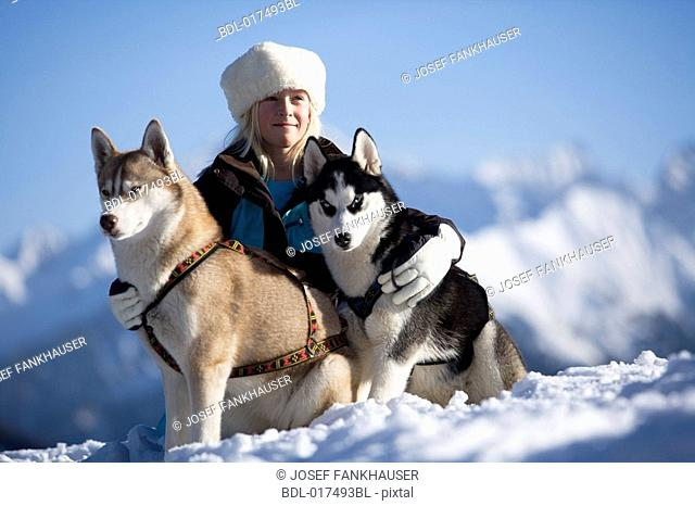 girl posing for a portrait with her two huskies in the mountains