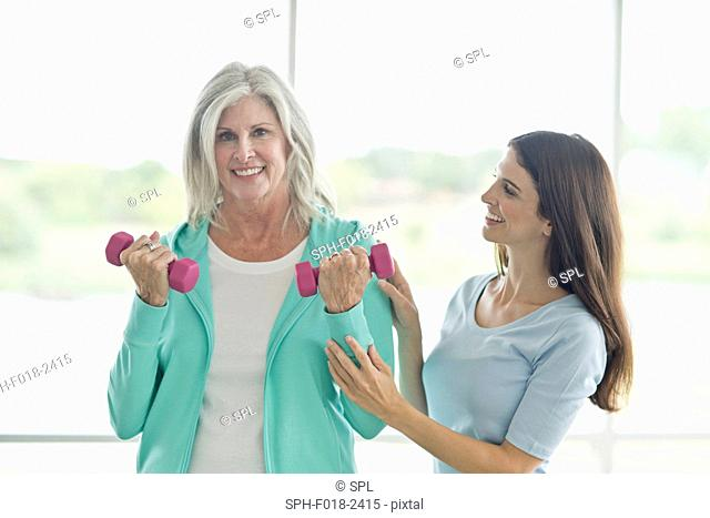Senior woman using hand weights with personal trainer