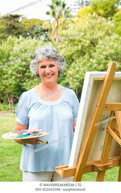 Smiling mature woman painting on canvas