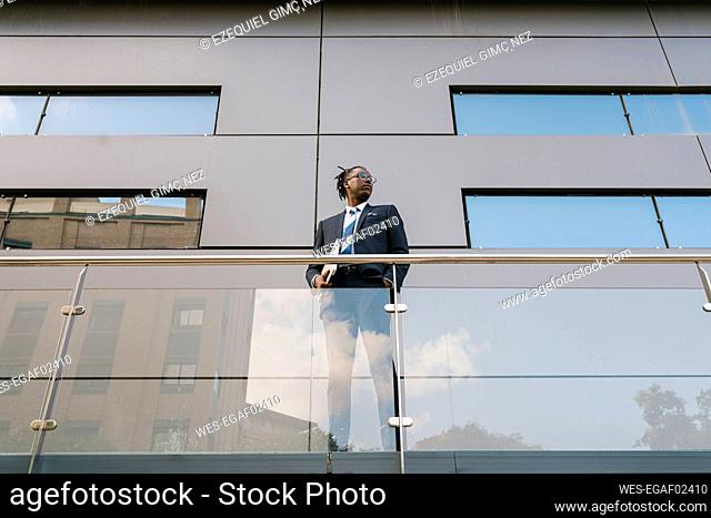 Businessman holding laptop while standing at office building