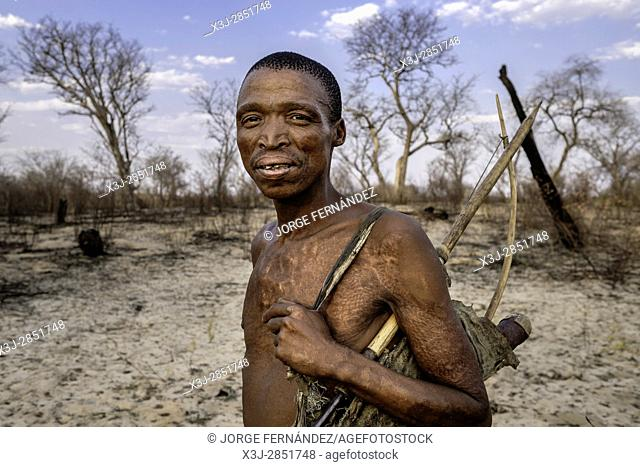 Portrait of Mr. Cqunta with bow and arrow wearing his traditional attires to entertain the tourists in which we can see the burned landscape and the scars in...
