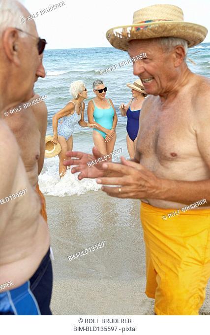 Senior men talking on beach