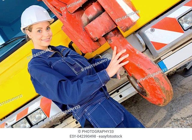 woman worker posing holding on to crane hook