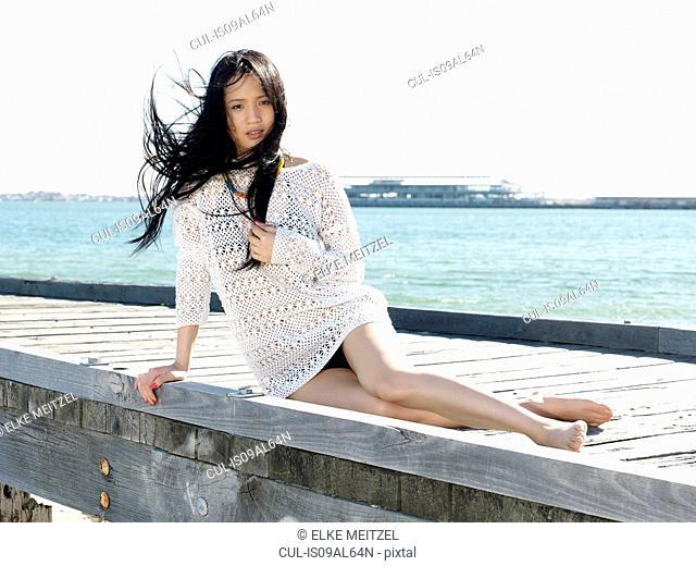Portrait of young woman reclining on pier, Port Melbourne, Melbourne, Victoria, Australia