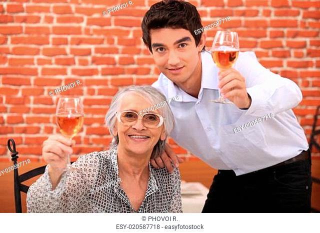 senior lady and young man making a toast
