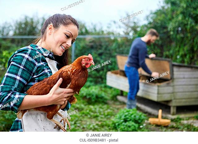 Young couple in chicken coop holding chicken