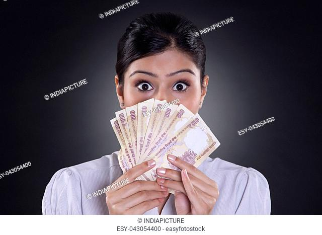 Portrait of businesswoman holding currency