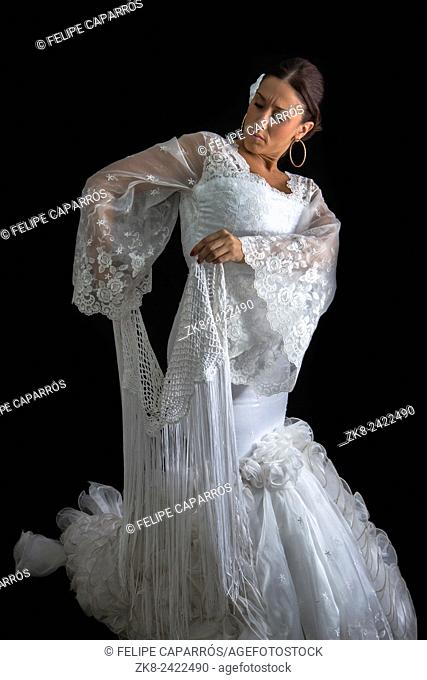Flamenco dancer with white dress and hands crossed up on his back on black background