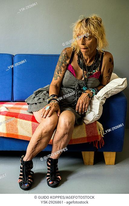 Tilburg, Netherlands. Mature adult caucasian woman, portrait, while sitting on a living room sofa