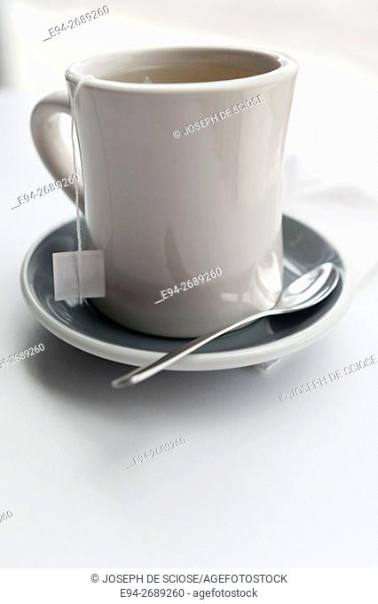 Saucer, spoon and tea cup on a white table