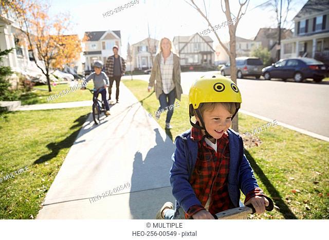 Smiling boy riding push scooter on neighborhood sidewalk