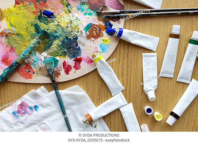 palette, brushes and paint tubes on table